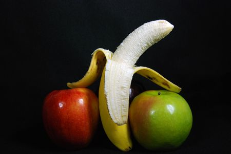 peeled banana: peeled banana between apples Stock Photo