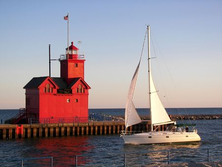 sailboat passing a red lighthouse photo