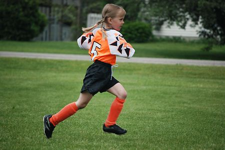 pigtail: young soccer player running on the field