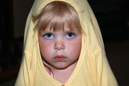 Child with strecthed out sweater over her head.