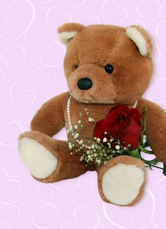 Teddy bear wearing pearls with red rose. photo