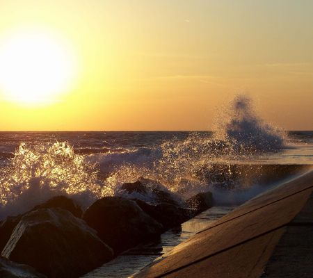 golden  gleam: Waves crashing over the pier at sunset.