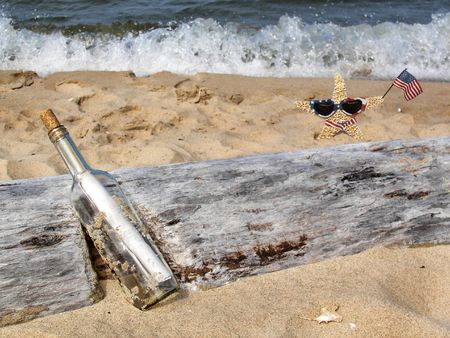 Message in a bottle with starfish and driftwood. photo