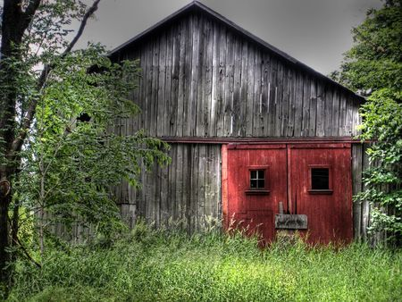 dilapidated: Red doors on an old dilapidated barn.