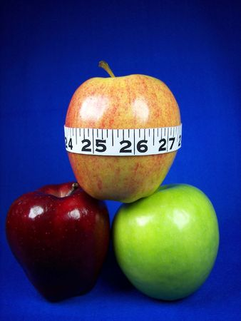 Measure tape around a stack of apples.