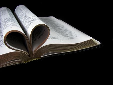 Curled pages of a Bible in a heart shape.