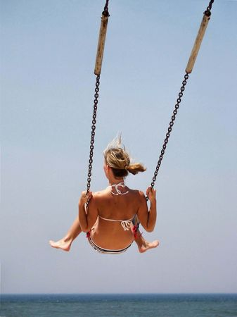 Young girl on a beach swing. Stock Photo