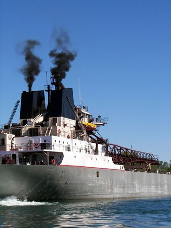 Smoke billowing out of freighter stacks.