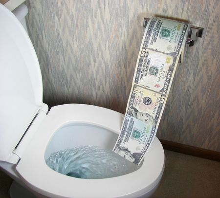 Money going into a toilet. Imagens