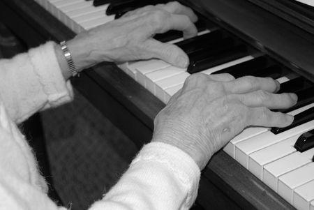 arthritic: Arthritic hands playing the piano. Stock Photo