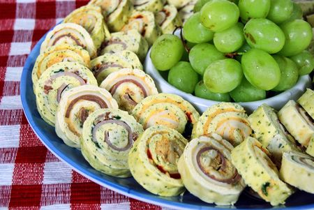 Party appetizers and grapes on red checkered cloth. Stock Photo