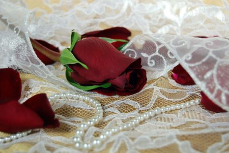 Red rose and pearls on lace and gold satin.