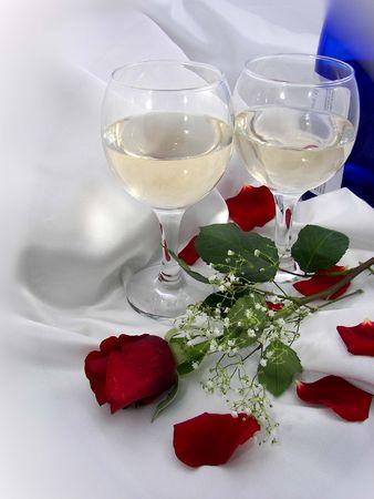 Wine bottle, glasses, and rose on satin. photo