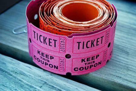 raffle ticket: Roll of raffle tickets on a wood table.