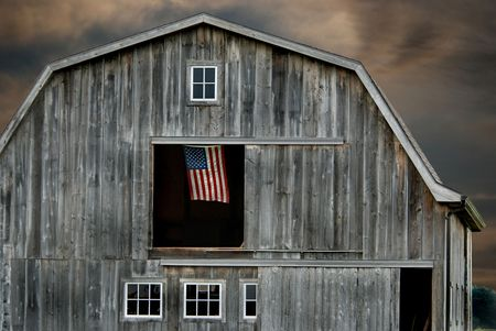 farm structure: American flag flying in a hayloft window.