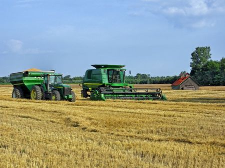 Farm equipment harvesting wheat.