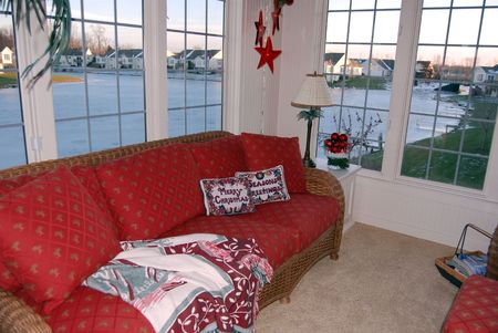 view of an elegant red couch: Porch room overlooking a lake at Christmas time.