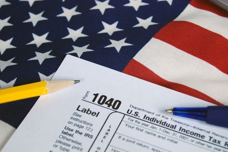 Tax form with pen and pencil on flag.