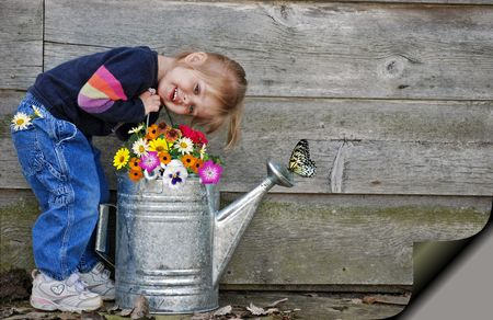 geranium color: Young child with blooms,  and watering can. Stock Photo