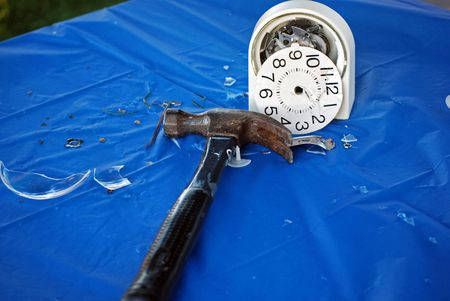 Hammer and smashed alarm clock on blue tablecloth. photo
