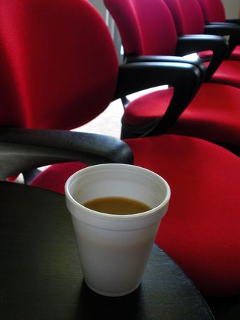 Cup of coffee and red chairs in a waiting room.