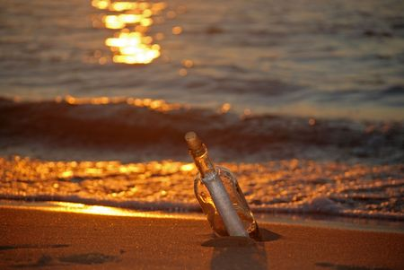 Mystery message in a wine bottle at sunset. Stock Photo - 3409157