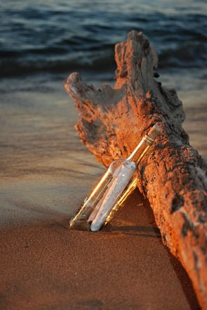 Message in a bottle and a driftwood log on the beach at sunset. Stock Photo - 3409158