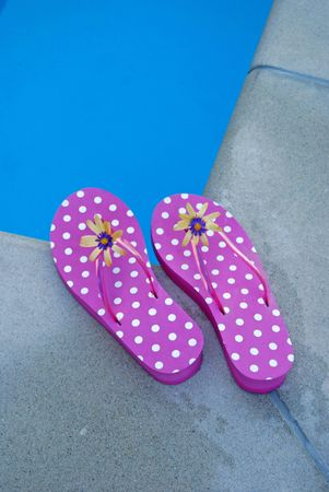 Summer flip flops at a corner of a swimming pool. Stock Photo