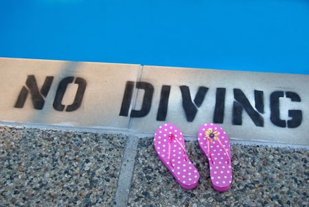 no diving sign: No diving sign and flip flops at the edge of the pool.