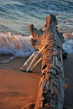 Message in a bottle leaning on driftwood. Stock Photo - 3422251