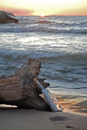 Message in a bottle propped on a driftwood log. Stock Photo - 3447102