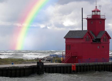 Rainbow after the storm behind a red lighthouse. Stockfoto