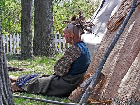 tepee: Young Indian brave leaning against his tepee.