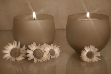 flickering: Flickering candles with daisies in sepia tones. Stock Photo