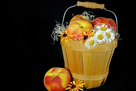 Peaches and flowers in a basket.