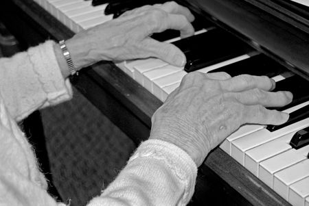 arthritic: Elderly woman with arthritic hands playing the piano. Stock Photo