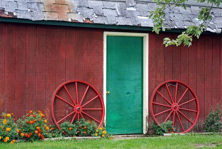 Bright green door of an old barn with wagon wheels.