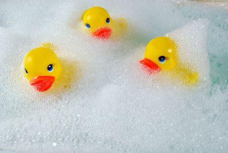 Rubber duckies in bubble bath. Stock Photo