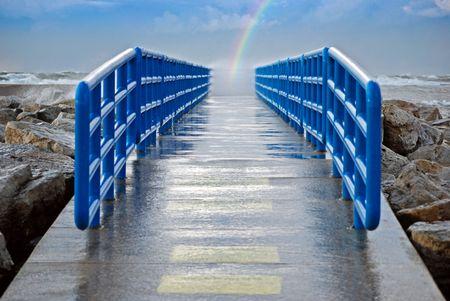 the end of a rainbow: Arco iris al final de un muelle h�medo.