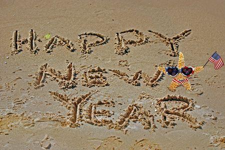 beach happy new year: Starfish with Happy New Year sign on beach. Stock Photo