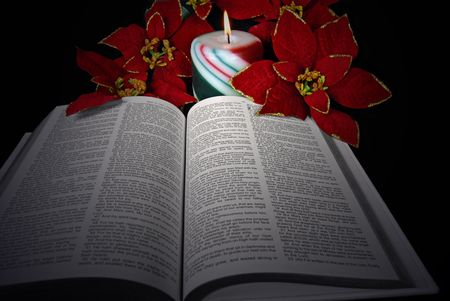 Illuminated Holy Bible with poinsettias and candle.