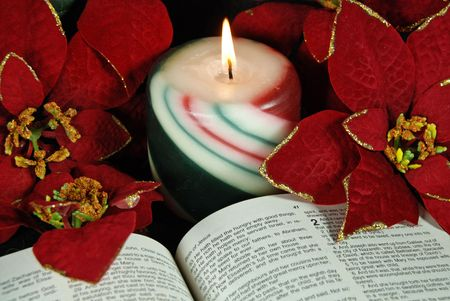 Glowing candle and poinsettias with open Bible.