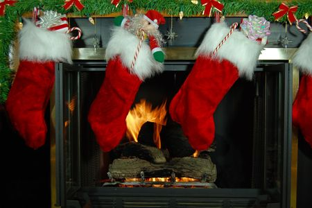 Stuffed holiday stockings hung by a fireplace.