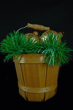 Gold ornaments and garland in bushel basket.