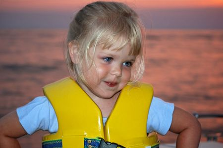 safe water: Little girl wearing a yellow life jacket while boating at sunset. Stock Photo