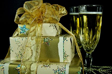 sheen: Fancy wrapped gifts with champagne filled flutes. Stock Photo