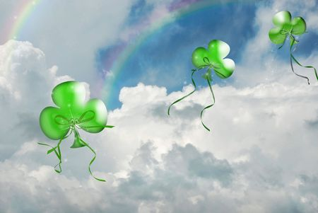 Floating shamrock balloons and rainbows in sky.