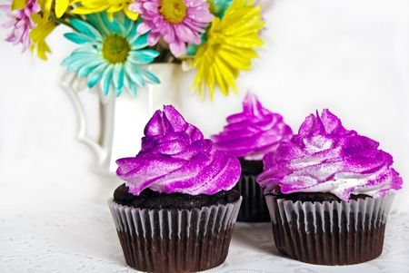 Fancy chocolate cupcakes with airbrushed frosting.