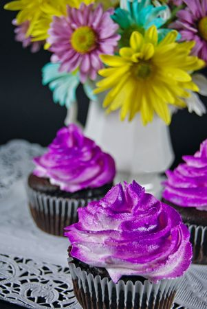 Purple airbrushed frosting on chocolate cupcakes.