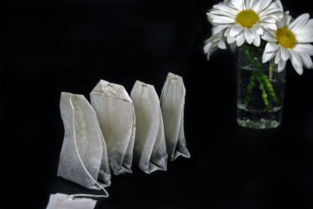 dainty: Row of tea bags with daisy bouquet. Stock Photo